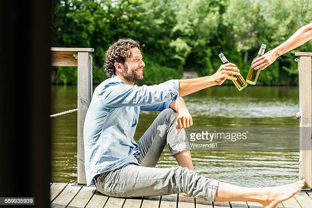 man sitting on platform at the waterside clinking beer bottle - houseboat stock pictures, royalty-free photos & images