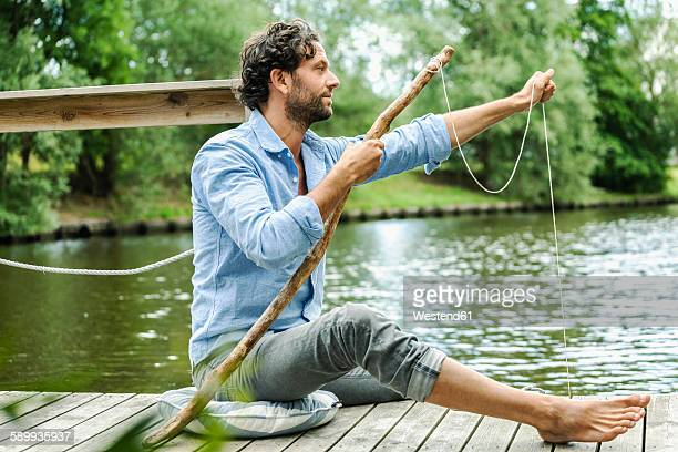 Man sitting on platform at the waterside with selfmade fishing rod