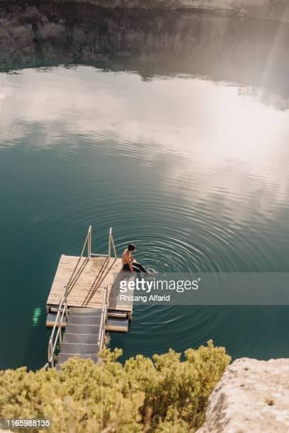 man sitting on platform on a lake - südaustralien stock-fotos und bilder