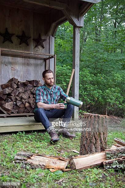 Man sitting on porch of log cabin
