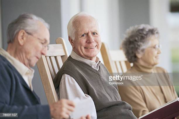 man sitting on porch with others - category:cs1_maint:_others stock pictures, royalty-free photos & images