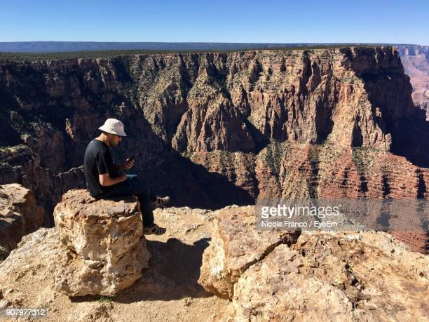 Man Sitting On Rock Against Clear Sky