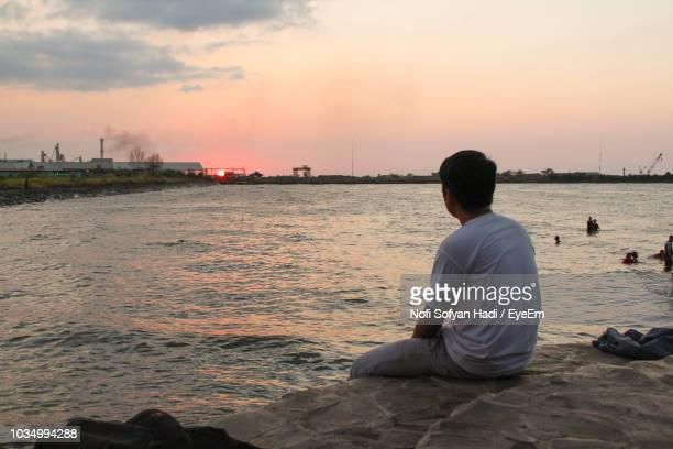 Man Sitting On Rock Against Sea During Sunset