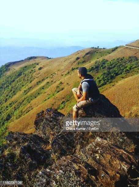 man sitting on rock against sky - karnataka stock pictures, royalty-free photos & images