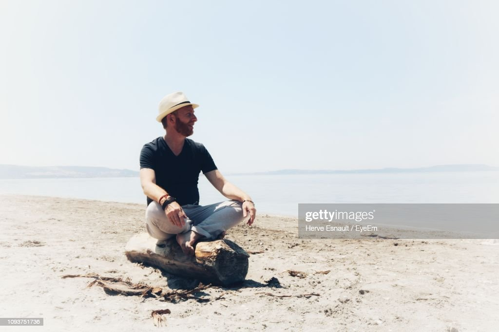 Man Sitting On Rock At Beach Against Clear Sky : Stock Photo