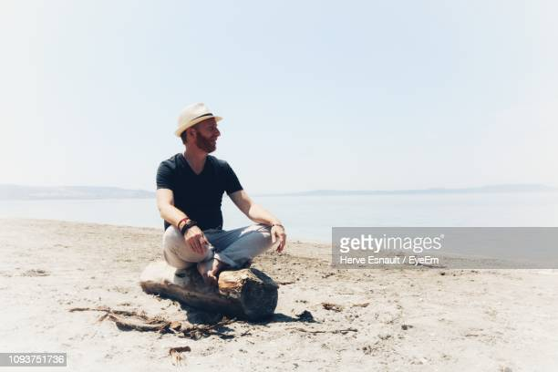 Man Sitting On Rock At Beach Against Clear Sky