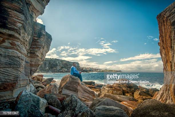 Man Sitting On Rock At Sea Shore Against Sky