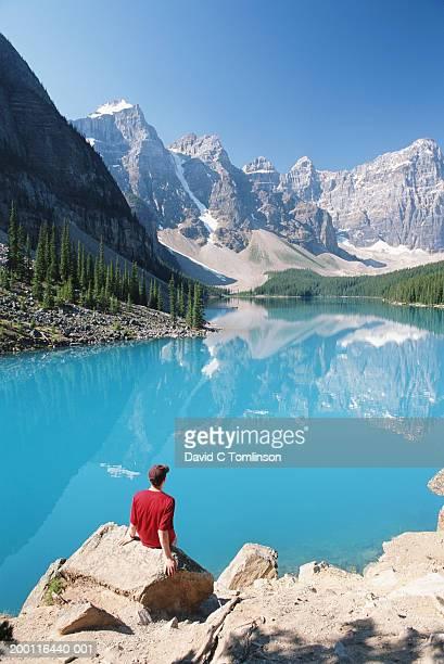 Man sitting on rock by lake reflecting mountains, rear view
