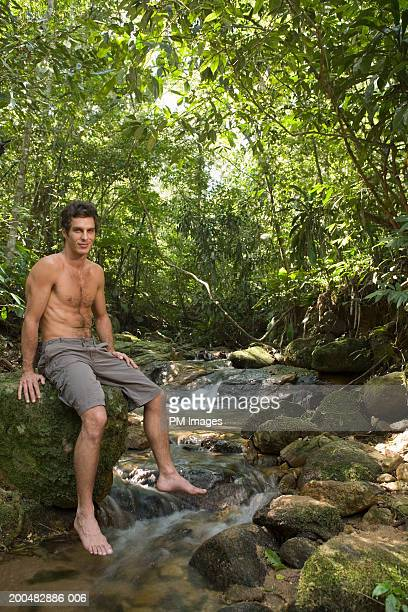 Man sitting on rock by stream above stream