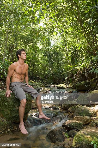 Man sitting on rock by stream above stream
