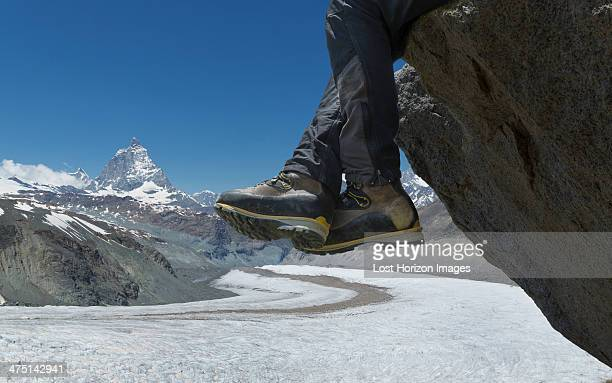 man sitting on rock by the matterhorn, zermatt, canton wallis, switzerland - white boot stock pictures, royalty-free photos & images