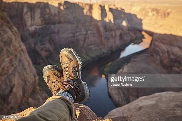Man sitting on rock, close-up of feet, Page, Arizona, USA