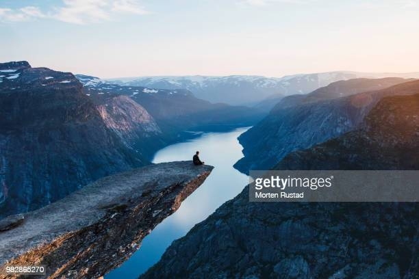 Man sitting on rock edge above river, Hardangerfjord, Hordaland, Norway