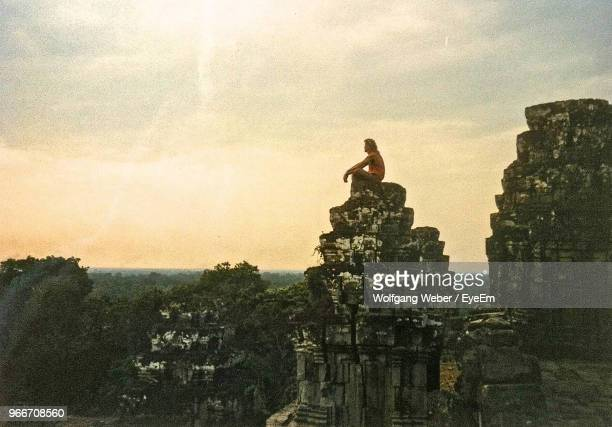 Man Sitting On Rock Formation Against Sky During Sunset