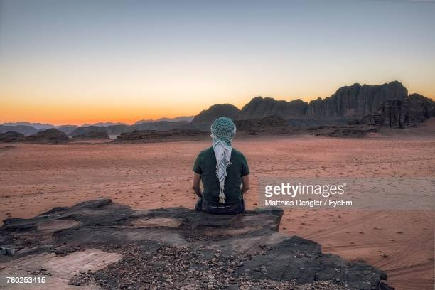 man sitting on rock in desert against sky during sunset - jordan middle east stock pictures, royalty-free photos & images