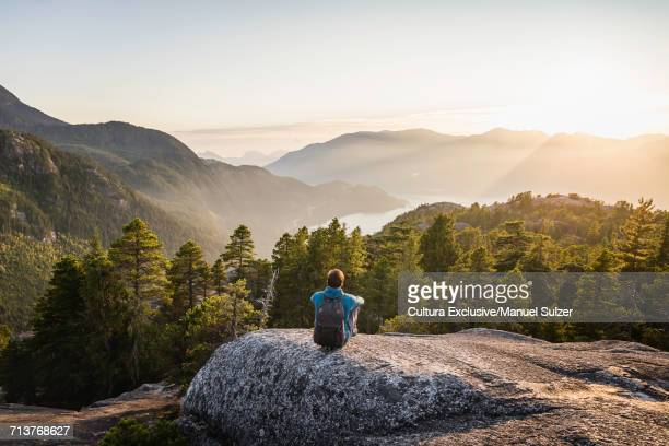 Man sitting on rock, looking at view, Stawamus Chief, overlooking Howe Sound Bay, Squamish, British Columbia, Canada