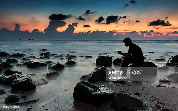 Man sitting on rock with gadget