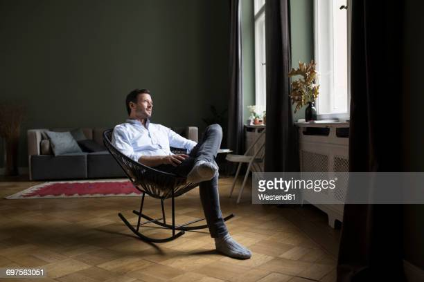 man sitting on rocking chair in his living room looking through window - rocking chair stock pictures, royalty-free photos & images