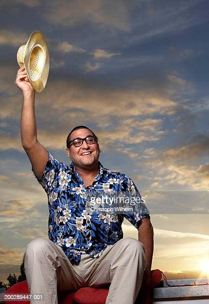 Man sitting on roof, raising hat, sunset