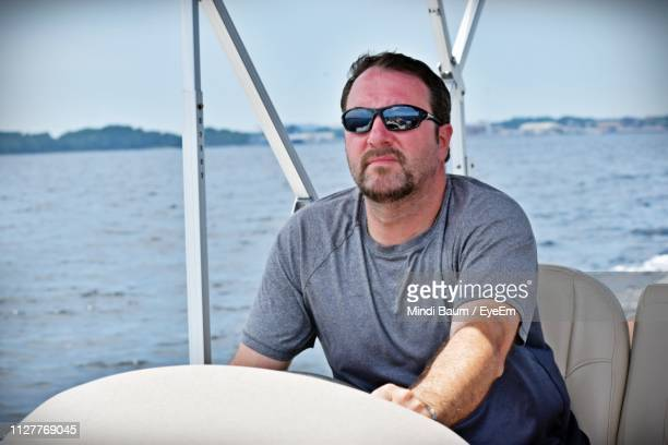 man sitting on sailboat in sea - baum stock pictures, royalty-free photos & images