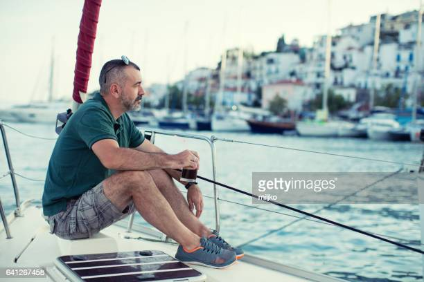 Man sitting on sailboat's bow and enjoying