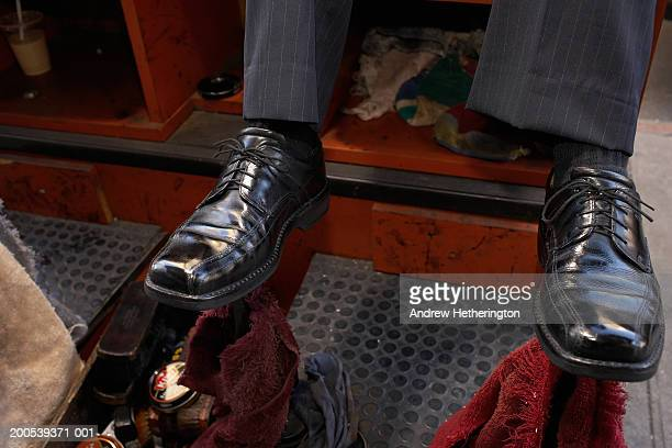 Man sitting on shoeshine chair, close-up, low section