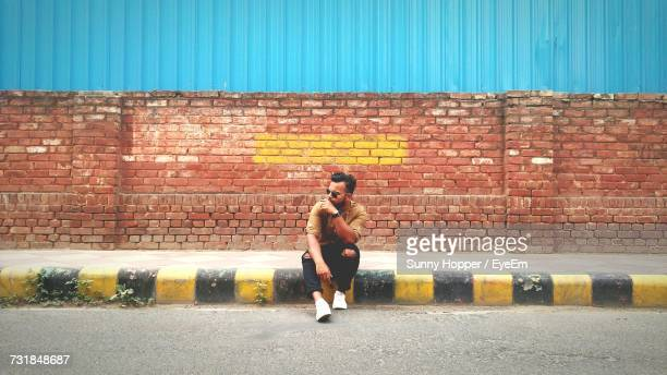 man sitting on sidewalk by road against wall - delhi stock pictures, royalty-free photos & images