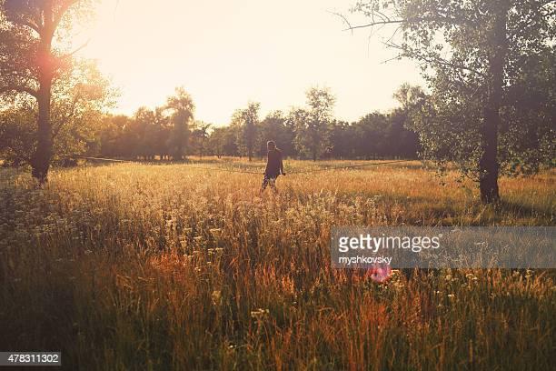 男に座る slackline in the meadow 夕暮れ時です。