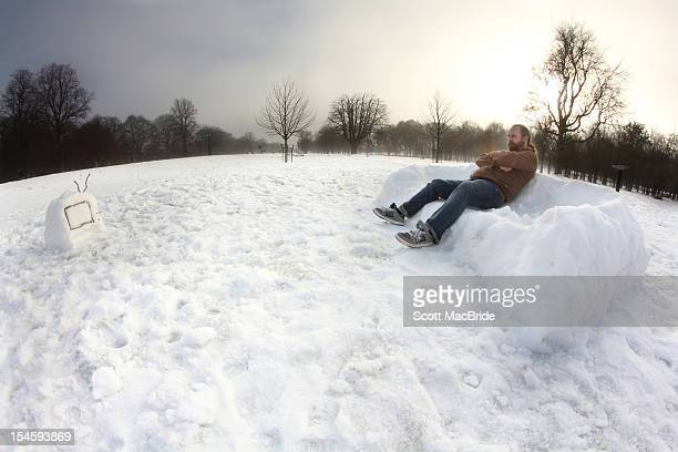 man sitting on snow - scott macbride stock pictures, royalty-free photos & images
