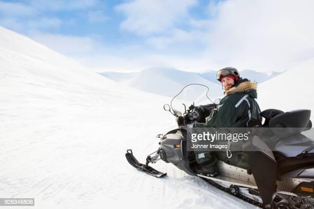 man sitting on snowmobile - snowmobiling - fotografias e filmes do acervo