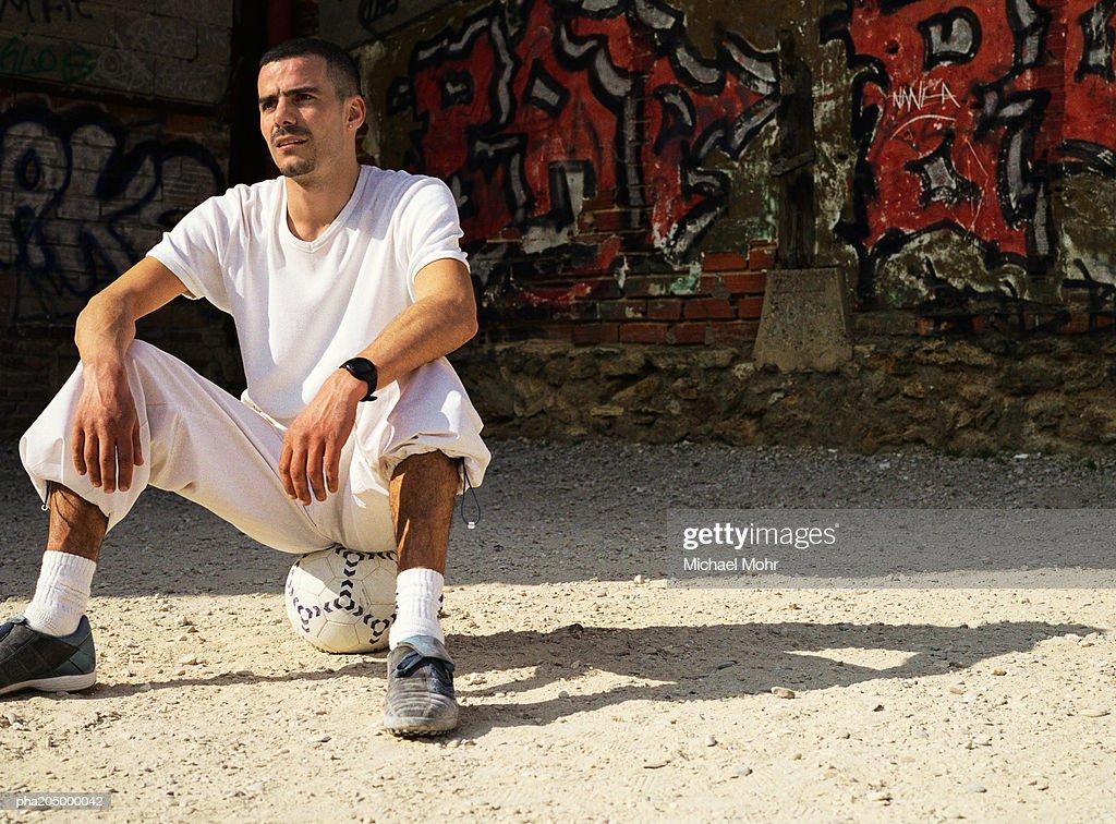 Man sitting on soccer ball : Stockfoto
