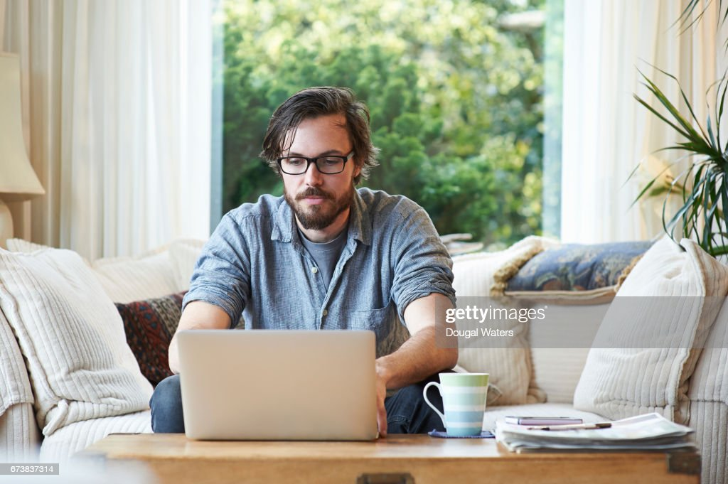 Man sitting on sofa and using laptop at home. : Stock Photo