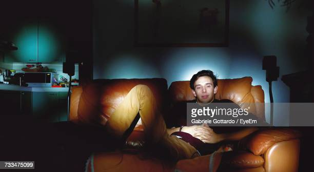man sitting on sofa at home - italian man stock photos and pictures