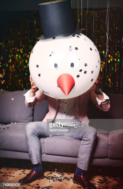 man sitting on sofa at party, holding snowman head in front of face - funny christmas stock-fotos und bilder