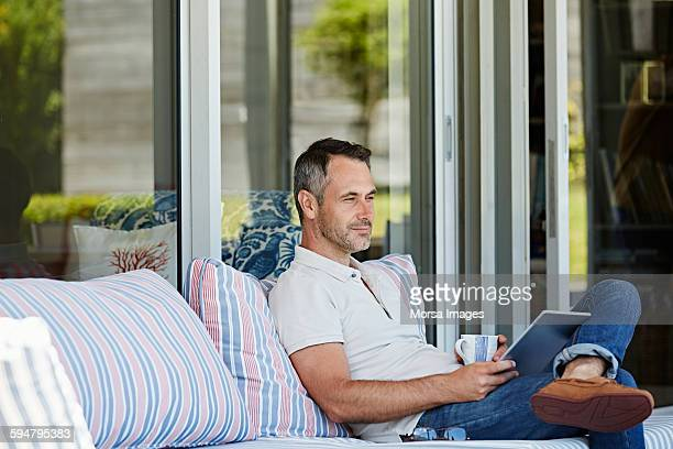 man sitting on sofa at patio - printed sleeve stock pictures, royalty-free photos & images