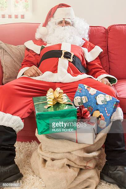 Man sitting on sofa dressed as santa claus with sack of christmas gifts