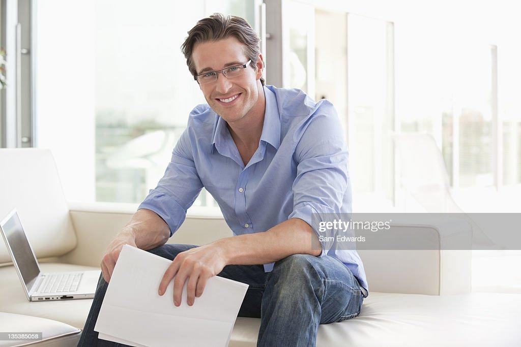 Man sitting on sofa holding paperwork : Stock Photo