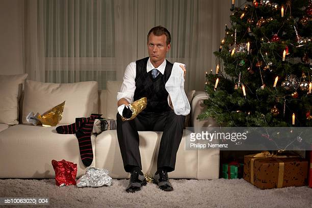 Man sitting on sofa holding sock, portrait