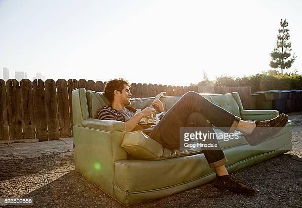 Man sitting on sofa in backyard playing guitar