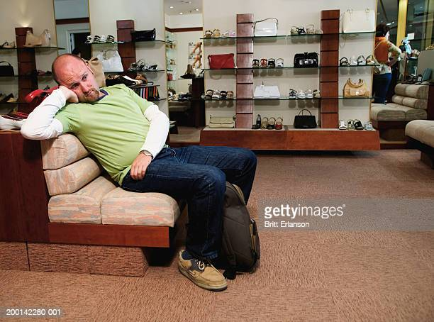 Man sitting on sofa in shoe shop, leaning back