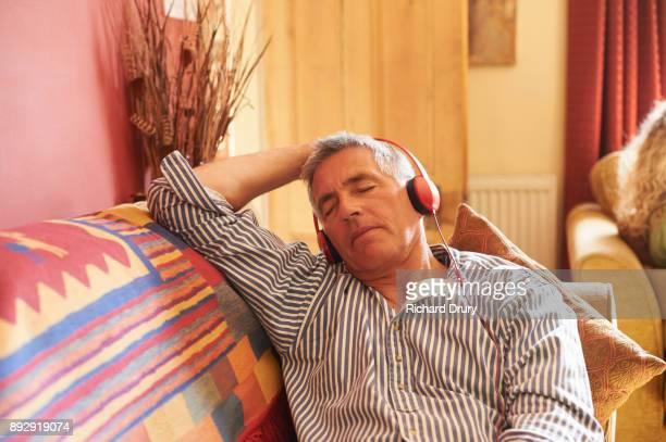 Man sitting on sofa listening to music