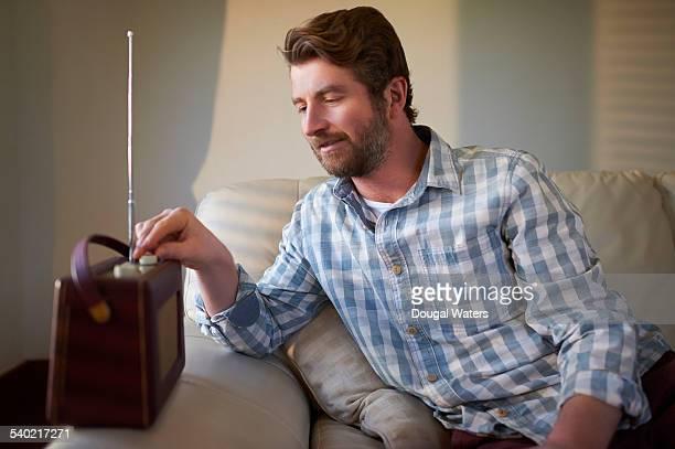 Man sitting on sofa listening to radio.