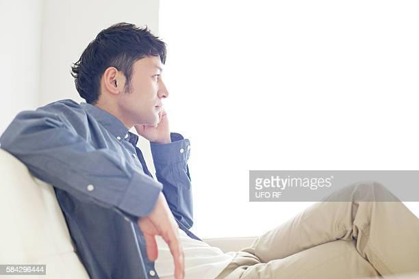 man sitting on sofa - チノパンツ ストックフォトと画像