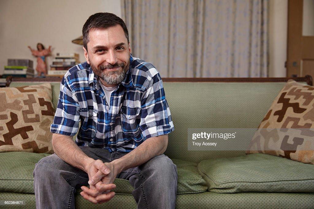 man sitting on sofa : Stock-Foto