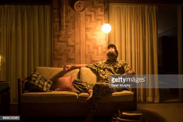 man sitting on sofa - wasting time stock pictures, royalty-free photos & images