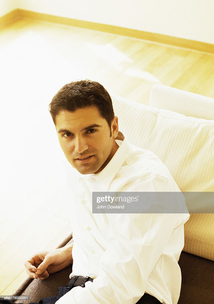 Man sitting on sofa, portrait : Stockfoto