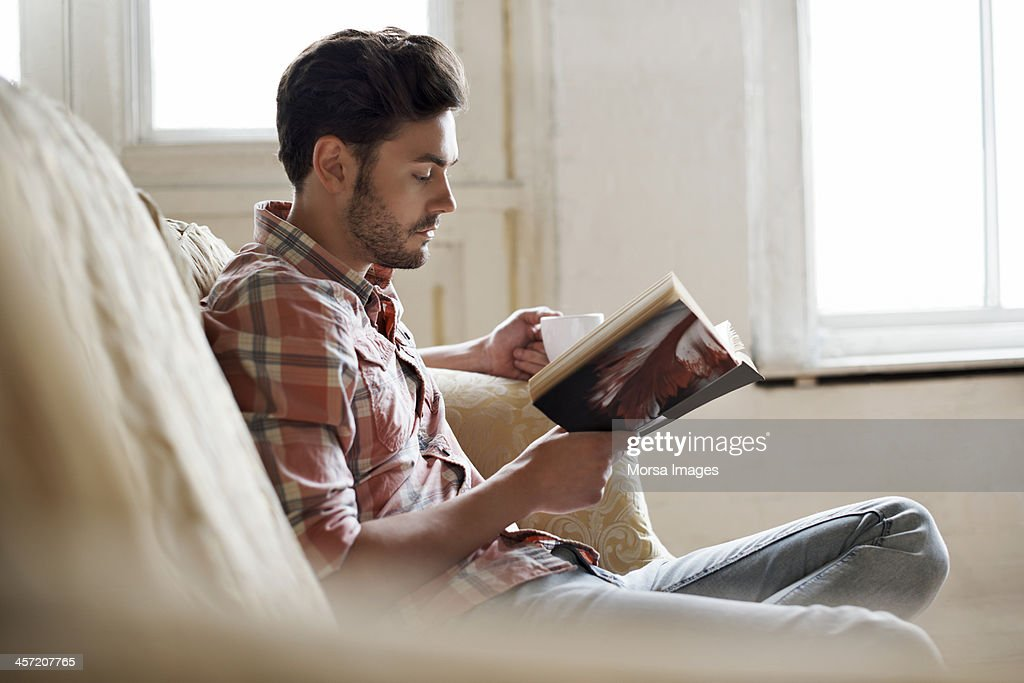 Man sitting on sofa reading book : Stock Photo