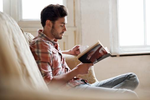 Man sitting on sofa reading book 457207765