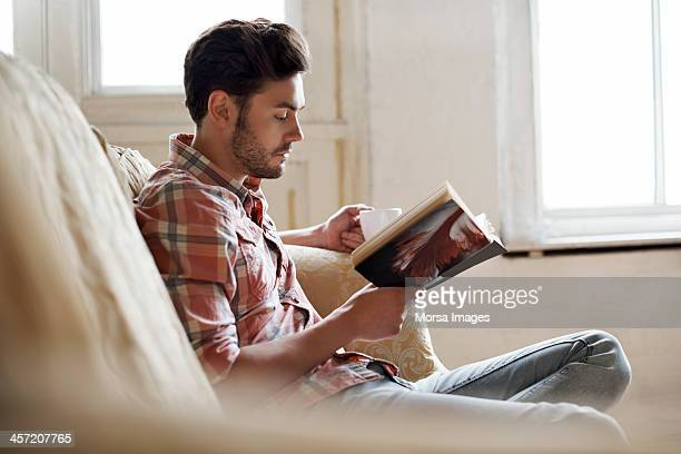 man sitting on sofa reading book - boek stockfoto's en -beelden