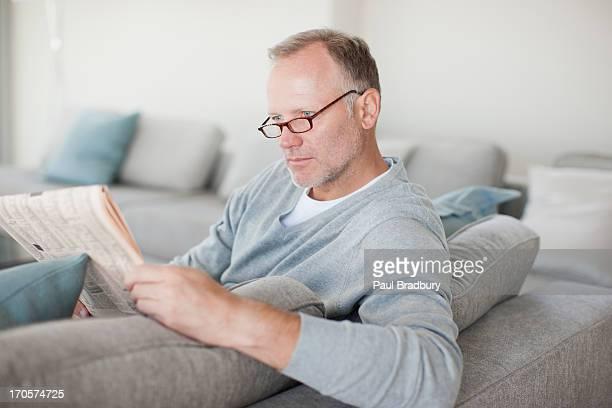 Man sitting on sofa reading newspaper